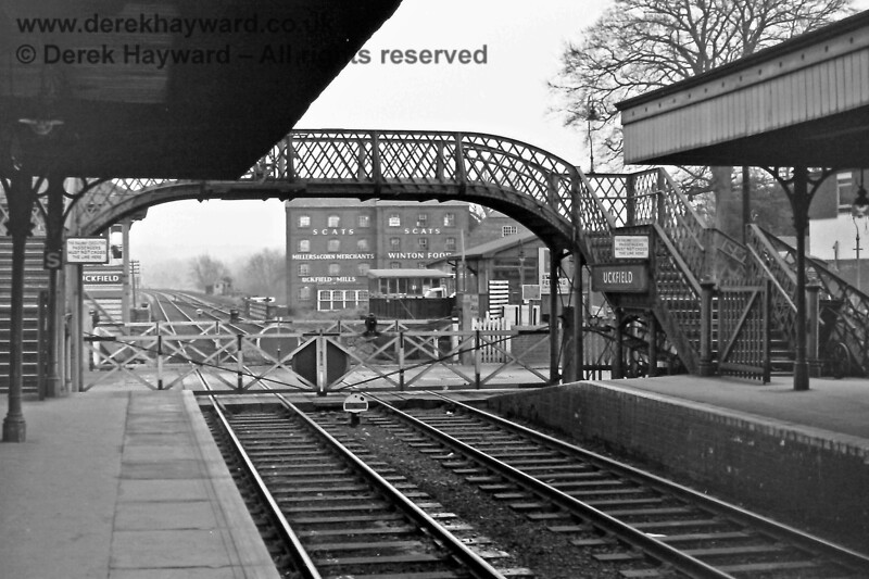 Uckfield footbridge and level crossing, looking north on 30.12. 1969.  The ground signal applies to the Down line and protects the level crossing.  The main Up Starting signal is hidden by the canopy.  Eric Kemp retains all rights to this image.