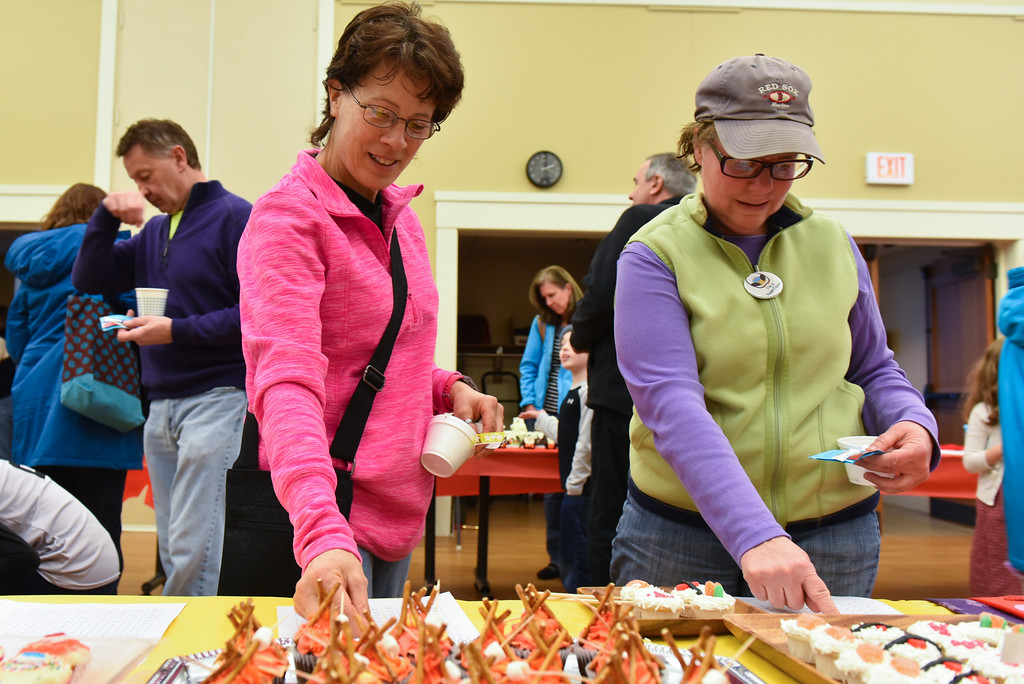 . (02/11/18 TOWNSEND MA) Nancy Moreau (left) of New Ipswich NH and Donna Larson of Townsend cast their vote at the Townsend Public Library\'s Cupcake Festival on Sunday. SENTINEL & ENTERPRISE JEFF PORTER