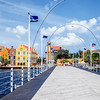 The Queen Emma Bridge in front of the colourful buildings on the Punda District in Willemstad, Curacao.