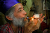 Rickie lights up a cigar with his Santeria hat and his alter behind him.