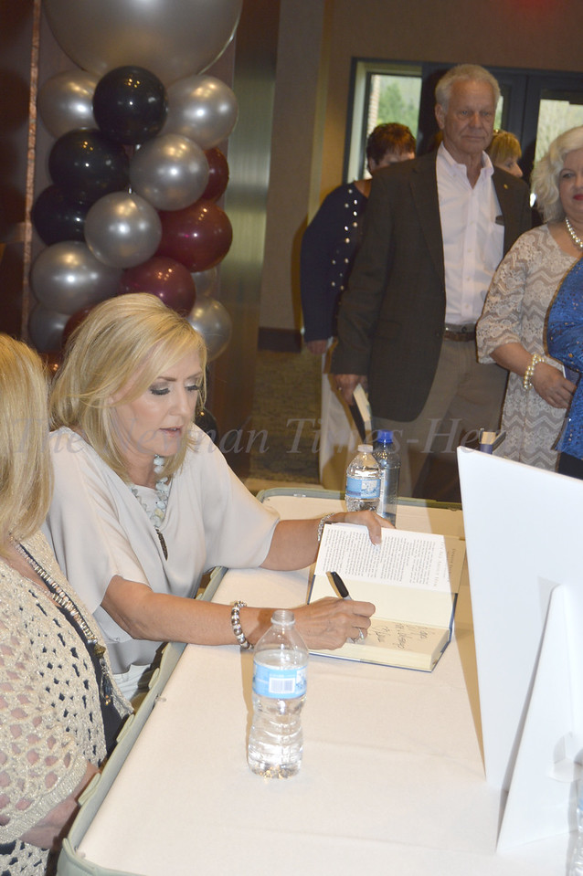 Photo By Maggie Bowers<br /> Denise Jackson, wife of country music star Alan Jackson, signs books at the recent Grey Matters Dinner Event benefitting the couple's nonprofit organization, Can't Never Could.