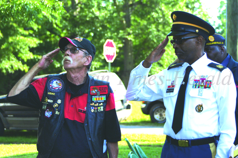 Leon Dyers (left) and Daniel Williams (right) salute the flag during the Memorial Day Program sponsored by the Grantville Veterans Association on Monday morning.