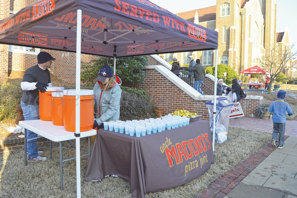 Photo by Maggie Bowers<br /> Maddio's Pizza representatives offer runners refreshments and snacks Saturday morning for Newnan's annual Run for Angels race.