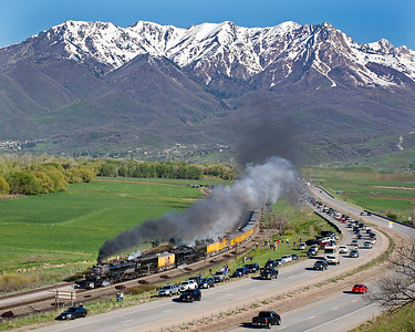 """May 12, 2019.  I have a love hate relationship with this image.  This was between Mountain Green and Peterson east of Ogden and Weber Canyon.  It is such a beautiful scene, but the  freeway and all the parked cars certainly change the ambience!  Freeway traffic following the trains was unlike anything I had seen.    If you look closely you will see a Utah Highway Patrol car leading the pack, preventing anyone from passing, so traffic backed up for miles.  In talking to a Morgan County Deputy who was patrolling the road where I was parked, law enforcement was primarily concerned with safety (speed) and was going to let folks park pretty much anywhere, so long as it was off the pavement.  The electronic info signs along the freeway warned of """"event traffic"""", That was something of an understatement.  It was quite a zoo, but for the most part folks were well behaved.  And it was also nice to see families bringing their kids out to see the train."""