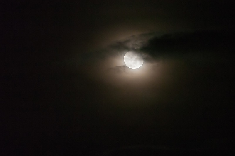 """06-06-2012 """"The Left Eye of God""""<br /> <br /> He does not seem very happy right now... It is easy to see stuff in the lightplay of the moon on a night like this, where the thin veil of fog and some fast and low clouds are free to play.<br /> <br /> This, to me, looked like an imposing and severe eye, looking down on us: poor, pretentious and for the most part not very well behaved human race.  I can only hope that if there is a big eye like this out there, it has a gentler disposition!"""