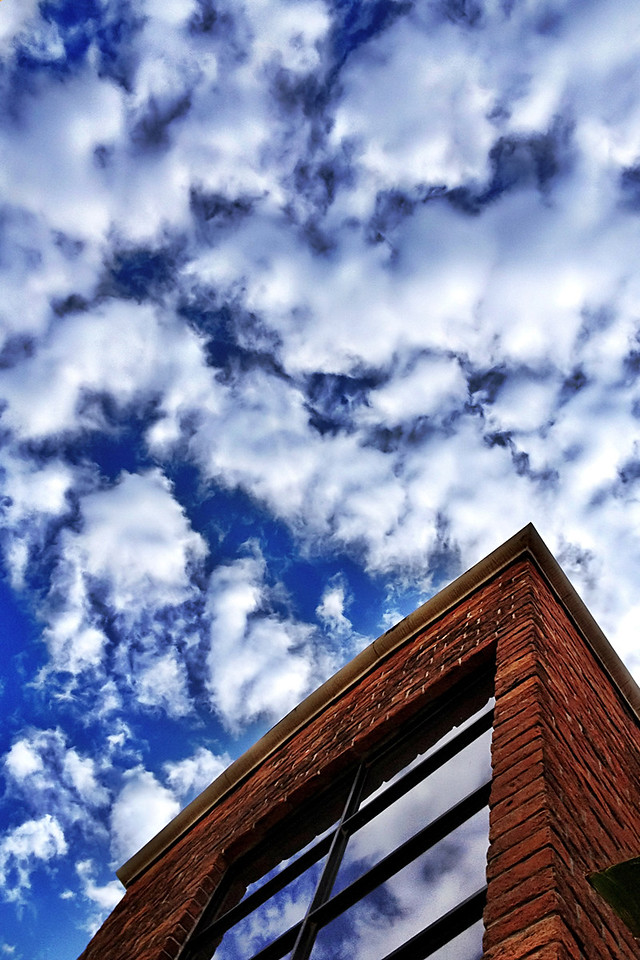"07-25-2012 ""Bricks, Glass, Clouds and Sky""<br /> <br /> It would seem that the ""look up"" policy is paying off recently.  I walked out to the garden since it was fresh and was welcomed by the breeze and this awesome sky.<br /> <br /> I felt quite compelled to catch in the most faithful way this moment and share it.  To me it represents how small we are in comparison to what nature can do: sure, our buildings and creations are awesome, but nature is in completely different league!<br /> <br /> The closest we got here was to reflect a little of this marvel on the glass..."