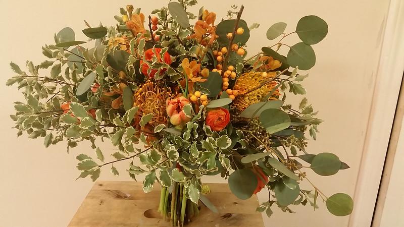portrait bouquet consisting of silver dollar eucalyptus, seeded eucalyptus, crinkled pittosporum, orange double tulips, orange ranunculus, orange mokara orchids, orange pincushion & orange berries