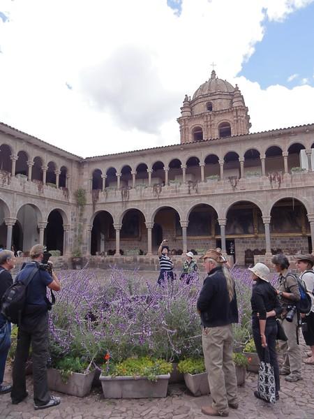 "Cathedral courtyard with Inca ""bathtub"" hidden behind purple flowers."