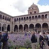 "Cathedral courtyard with Inca ""bathtub"" hidden behind purple flowers."