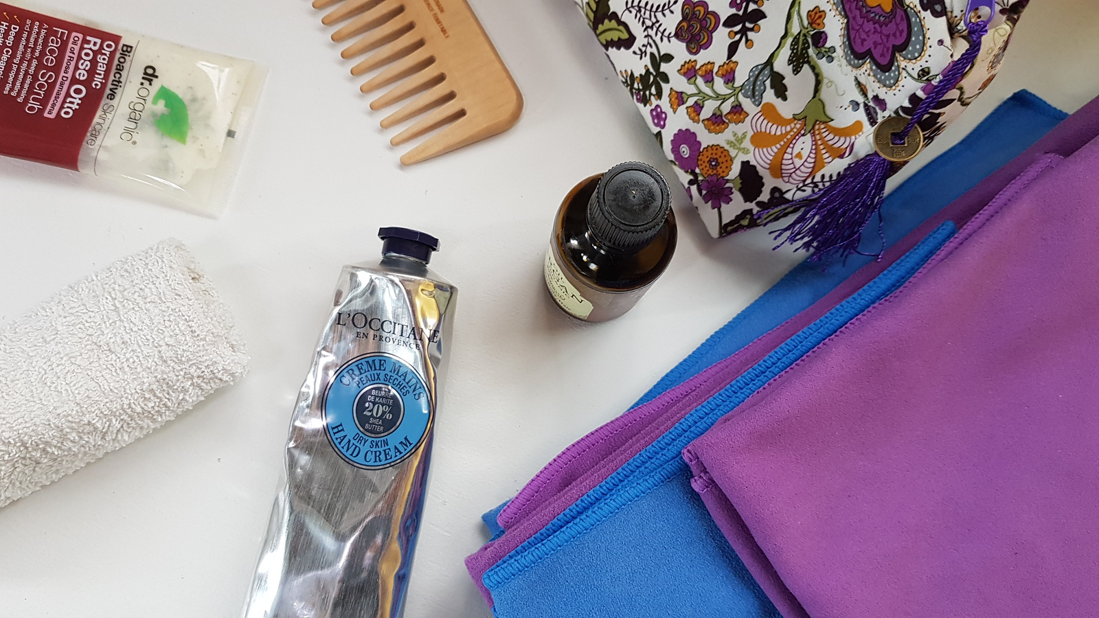 Van Life Bathroom Essentials: blue & purple microfibre towels, wooden combs, Argan Oil, rose face scrub, Loccitane hand cream, face cloth and flower decorated cosmetic bag