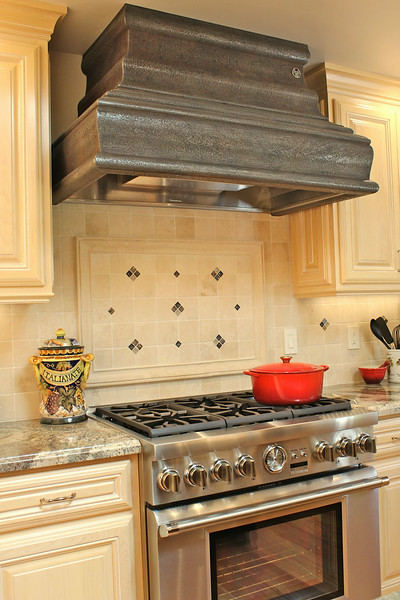 The  range and hood together, create a unified focal point that livens up the overall design.