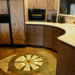 The base cabinets are veneered with plastic laminate. The floor is a highly reflective slate, with an assortment of stone set into it, in fanciful designs.