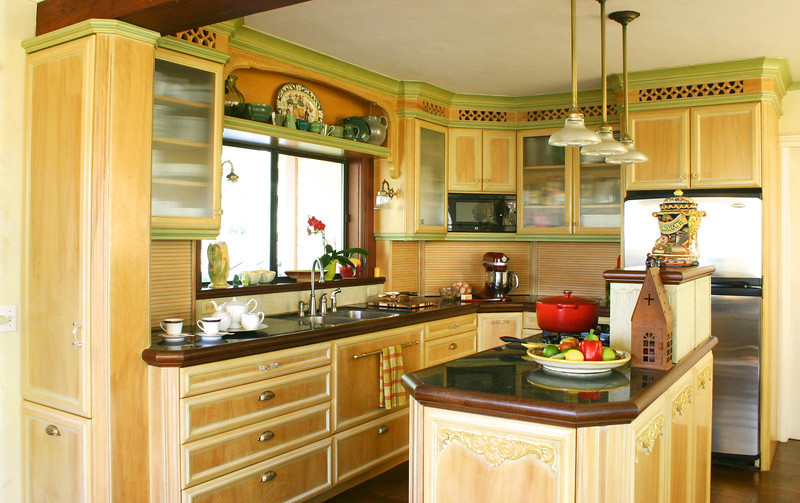 These pictures were taken sixteen years after this kitchen was installed, and it still looks as good as it did back then. Only the fridge, microwave, faucet and a pair of drawer slides have changed. The finish is hand brushed polyurethane over a wash of white latex paint, glazing and green latex accents.