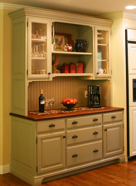 The hutch and island help to liven things up, with their dissimilar color and detailing. This also gives the kitchen the enduring charm of furniture collected over time.