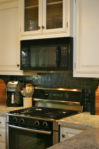This particular choice of glass and wall tile help the range and microwave to fit perfectly into their new environment.