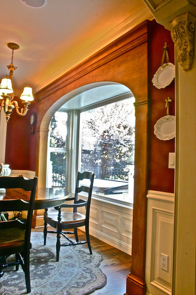 In the dining area, we built a large arch, using the same finish and styling as the kitchen. This effectively enhanced the lake view, and tied the room together