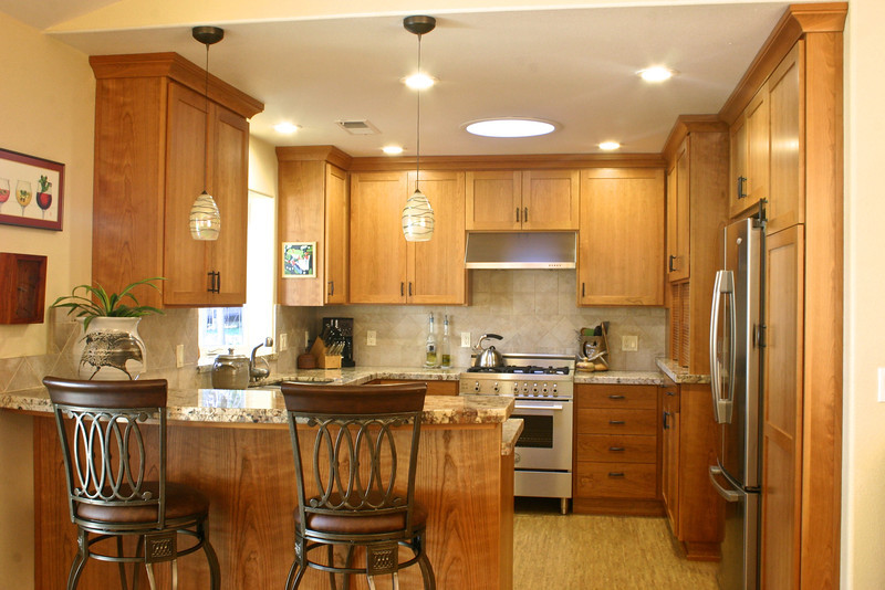 The stainless steel appliances, granite tops, ceramic tile, cork flooring and light ceiling and wall colors, all help to enrich the color of the cabinets.