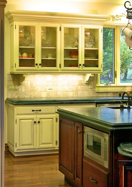 Other details, such as rope molding in the large crown, a molding detail under the upper cabinets, and seedy glass in one cabinet, help to add interest to the overall look.
