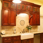 Stepping out the base and upper cabinets in the sink area add considerable interest to the design. Adding feet to the base cabinet, and an arched valance with some decorative touches, achieves the desired look.