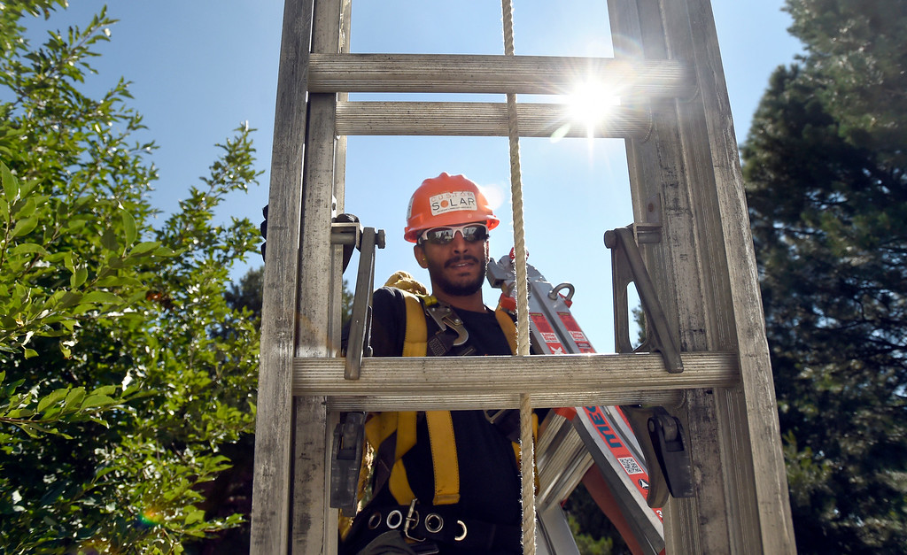 . Custom Solar Installation Lead Shravan Joshi carries equipment up a ladder while working to finish installing solar panels on a roof on Thursday in Boulder. For more photos of the installation go to dailycamera.com Jeremy Papasso/ Staff Photographer/ Aug 10, 2017