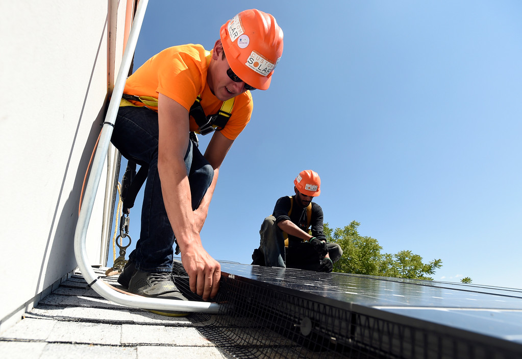 . Custom Solar installers Derek Barber, left, and Shravan Joshi work to finish installing solar panels on a roof on Thursday in Boulder. For more photos of the installation go to dailycamera.com Jeremy Papasso/ Staff Photographer/ Aug 10, 2017