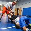Winnacunnet Wrestling Coach Eric Larcomb gives instructions to 12th grader Matt Cooney (red) and 9th grader Gage Bolduc during the Riptide Wrestling Youth Camp at WHS on Tuesday 7-26-2016.  Matt Parker Photos