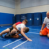 Winnacunnet Wrestling Coach Eric Larcomb watches as 12th grader Matt Cooney (red) performs a move on 9th grader Gage Bolduc during the Riptide Wrestling Youth Camp at WHS on Tuesday 7-26-2016.  Matt Parker Photos