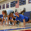 Winnacunnet Junior Katelyn Deyo is still smiling while giving her arms a workout doing push-ups as Taylor Nydam heads to the next station during Monday's practice on 8-29-2016 @ WHS.  Matt Parker Photos