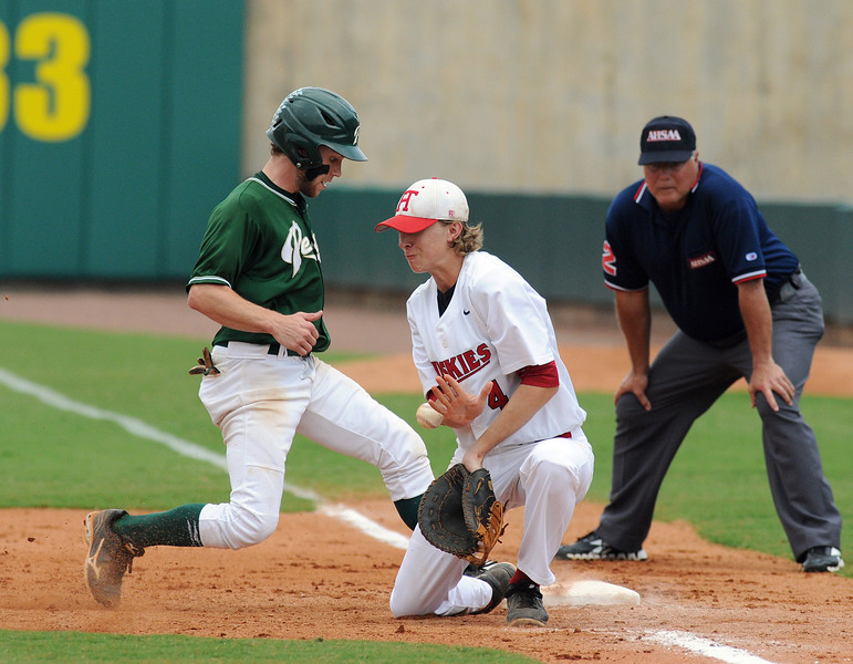 Pelham's Fletcher Johnson, left, jumps back to first as Hewitt-Trussville's Will Pharis mishandles the throw in a pick attempt in the 6A AHSAA state championship finale won by Pelham 1-0 over Hewitt-Trussville at Riverwalk Stadium in Montgomery, Ala., May 18, 2013.  By David Bundy