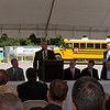 Blue Bird's president and CEO, Phil Horlock, speaks during the Hall County Schools ceremony. At far left is Todd Mouw, vice president at ROUSH CleanTech. Date: May 10, 2012