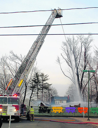 Manchester firefighters douse the remains of the automotive shop that exploded at 185 Main street on Friday February 10, 2012.  (Leslloyd F. Alleyne / Journal Inquirer).