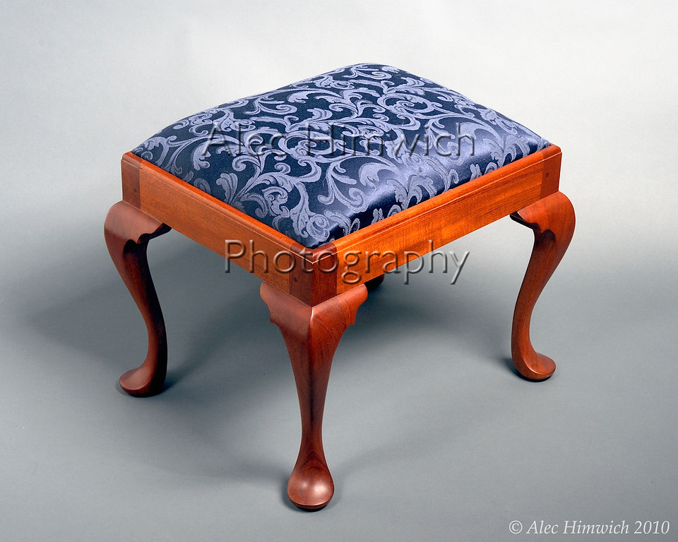 This Queen Anne style footstool incorporates padfoot style cabriole legs that are hand cut and hand carved.  It is modeled after a piece in the Winterthur Museum.  The upholstery is foam with cotton lining and brocade covering.  The wood is Honduran mahogany with shellac finish.