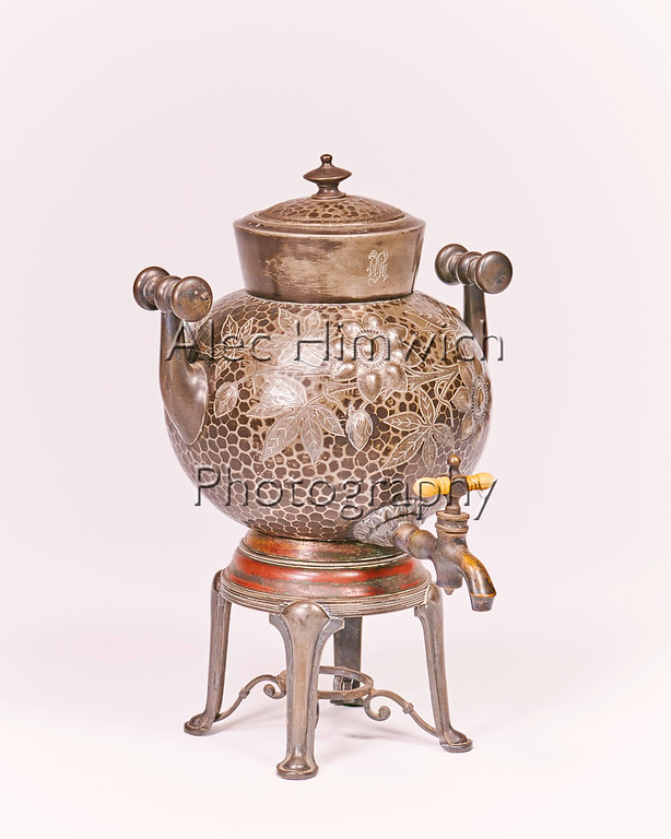 """This samovar is from the New York city home of my paternal grandparents.  Adolph Himowich and Rose Igelska immigrated respectively from Keiv, Russia in 1881 and Suwalki, Poland in 1884.   They were married in 1891.   You can see the script """"H"""" on the collar below the Samovar top.  In those days without ubiqitous coffee shops, tea was more popular than today as a caffeine delivery vehicle."""