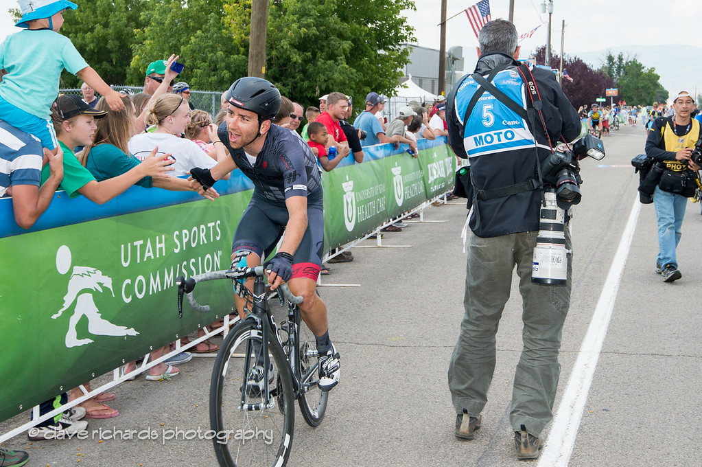 "Hincapie Team rider giving the ""low five"" to the fans along the finish line"