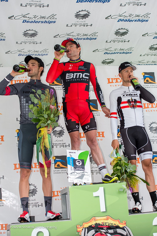 top three finishers on the podium quench their thirst