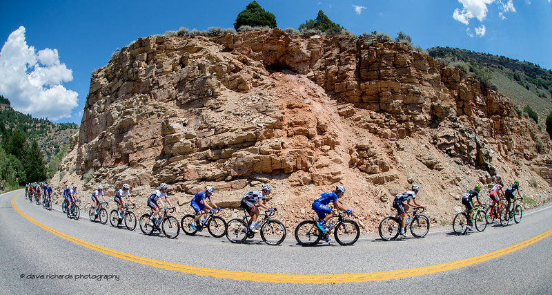 The peloton rides single file around rugged rock formation while descending Logan Canyon on Stage 1, Logan-BearLake-Logan,  2017 LHM Tour of Utah (Photo by Dave Richards, daverphoto.com)