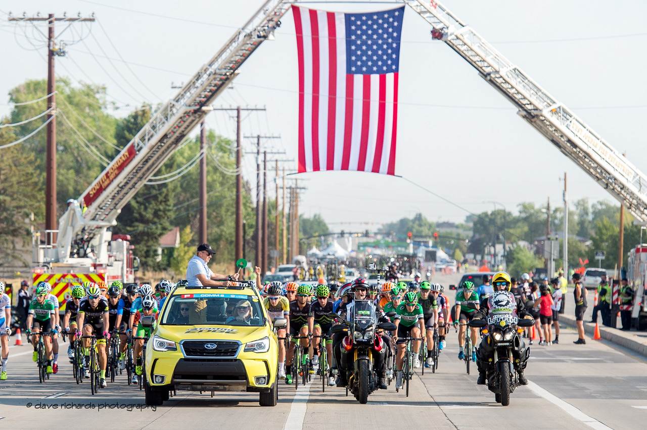 The peloton rolls out beneath a giant American flag  on Stage 4, South Jordan City to west desert Pony Express Route and back,  2017 LHM Tour of Utah (Photo by Dave Richards, daverphoto.com)