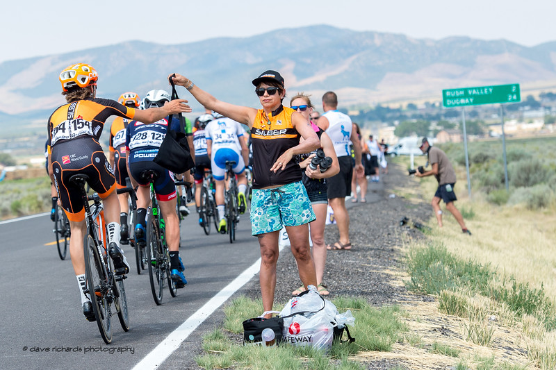 Veteran soigneur Lani makes the lunch handoff to  her Silber Pro Cycling rider. Stage 4, South Jordan City to west desert Pony Express Route and back,  2017 LHM Tour of Utah (Photo by Dave Richards, daverphoto.com)