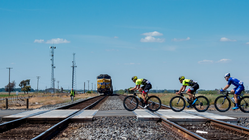 Look out! Train a comin'  Not really, the train came to a stop and the riders passed through safely. Men's Stage Five, Stockton to Elk Grove, 2018 Amgen Tour of California cycling race (Photo by Dave Richards, daverphoto.com)