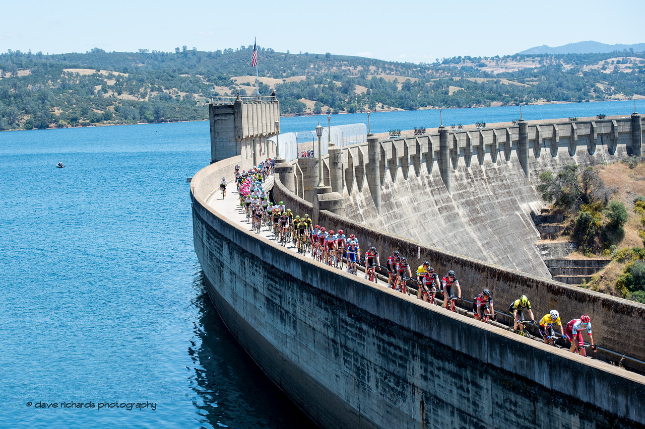 Riders of the peloton stretch out along the Pardee Reservoir dam. Men's Stage Five, Stockton to Elk Grove, 2018 Amgen Tour of California cycling race (Photo by Dave Richards, daverphoto.com)