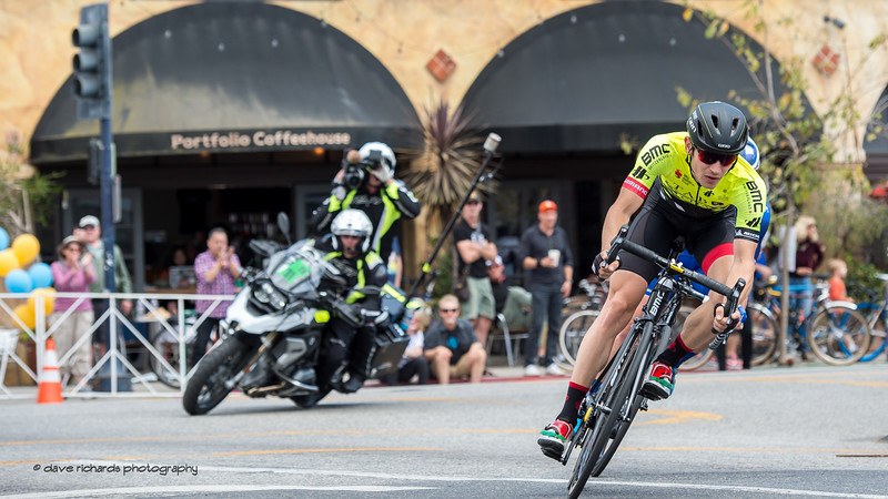 The breakaway nails a tight corner under the watchfull eye of the TV moto. Men's Stage One in Long Beach, 2018 Amgen Tour of California cycling race (Photo by Dave Richards, daverphoto.com)