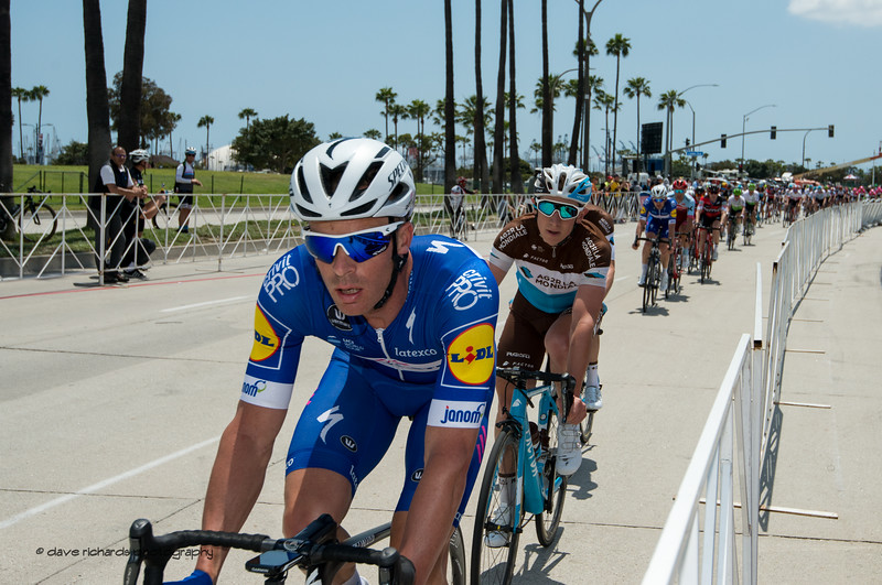 Up against the rails, the peloton hammers away. Men's Stage One in Long Beach, 2018 Amgen Tour of California cycling race (Photo by Dave Richards, daverphoto.com)