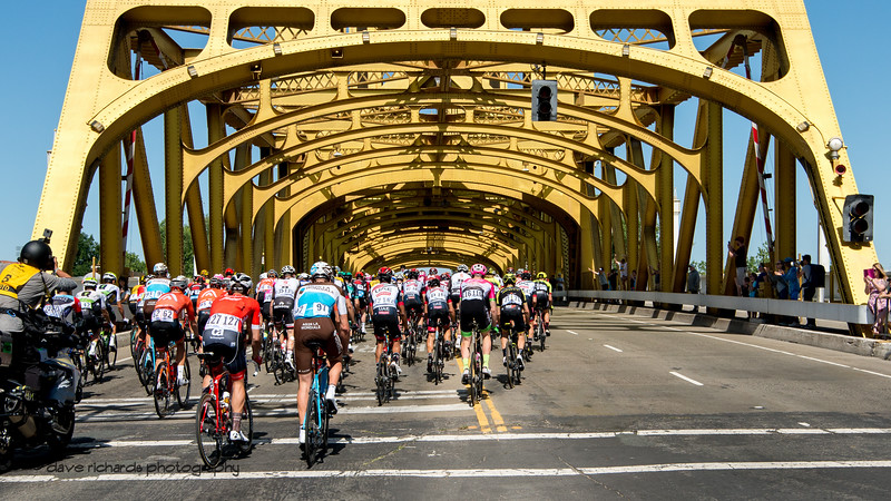 Riders pass under the historic Tower Bridge as they head out during the neutralized start of Men's Stage Seven, Sacramento, 2018 Amgen Tour of California cycling race (Photo by Dave Richards, daverphoto.com)