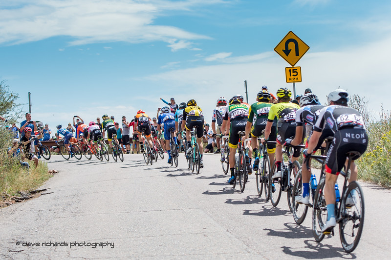 The peloton rolls up a short hill leaving Red Rocks park. Men's Stage 3 road course starting in Denver running out west up Lookout Mtn, then Red Rocks with a loop back to Denver. 2018 Colorado Classic cycling race (Photo by Dave Richards, daverphoto.com)