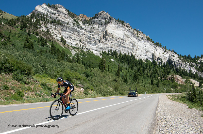 The Hellgate cliffs loom over Marko Pavlic (DC Bank Pro Cycling Team) as he rips the descent during the Prologue at Snowbird, 2019 LHM Tour of Utah (Photo by Dave Richards, daverphoto.com)