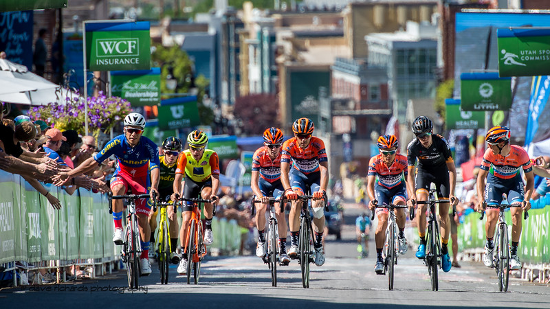 The final riders give high fives to the fans as they roll in to the finish line on Stage 6, 2019 LHM Tour of Utah (Photo by Dave Richards, daverphoto.com)