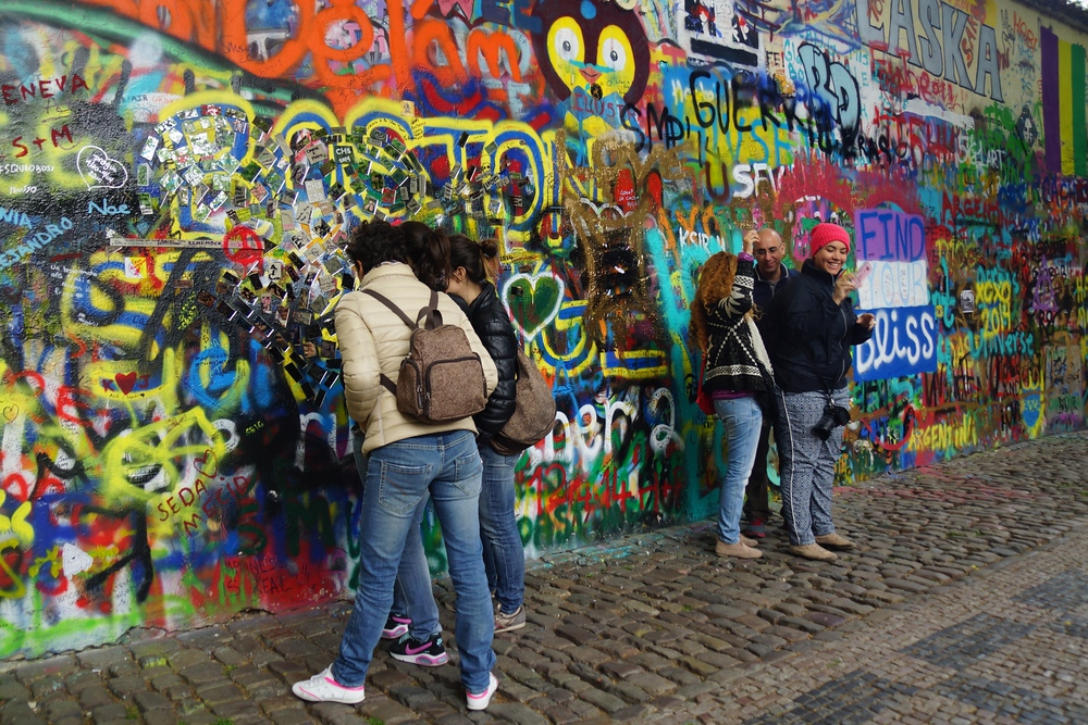 People hanging out by the John Lennon Wall in Prague, Czech Republic