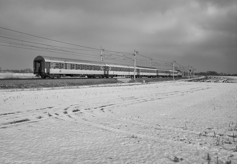 A České Dráhy train heads east from Prague across a snow covered field at Pardubice-Opočínek.
