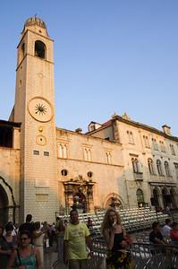 Městká zvonice Původní zvonice, postavená místními obyvateli, zde stála od 15. století. Bohužel musela být roku 1906 zbourána, protože hrozilo její zřícení. Zvonici znovu postavili až v roce 1929 podle plánů Pasko Baletina a finančního přispění Paska Baburici. Zvonice byla původně součástí rektorského paláce, ale dnes je 31 metrů vysoká věž od paláce oddělena. Kromě hodin ve tvaru chobotnice se na vrcholku věže nachází tzv. Zelenaci (maro a Baro). Dvě bronzové sochy vojáků z 15. století, kteří odbíjejí čas.  Dnes se však na vrcholku nacházejí kopie z 50. let 20. století. Originály jsou k vidění v atriu Sponza paláce.
