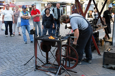 A blacksmith trying to impress his tourist guests with his skills on St. Wenceslas Square.
